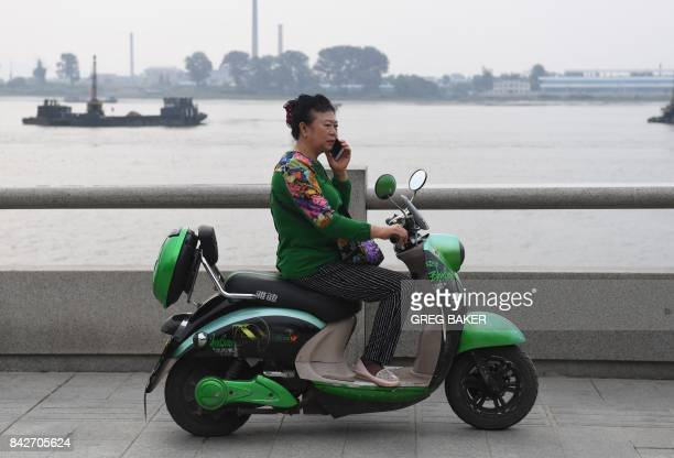 A Chinese woman makes a call from her motorcycle on the waterfront in Dandong in China's northeast Liaoning province opposite the North Korean town...