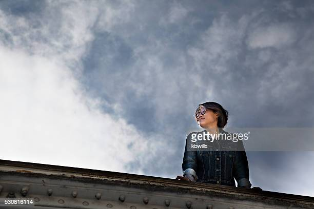 chinese woman on Paris bridge against threatening sky