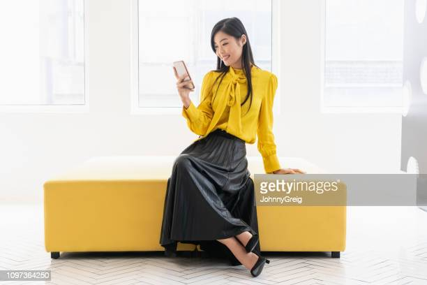 chinese woman on yellow bench with phone - colour block stock pictures, royalty-free photos & images