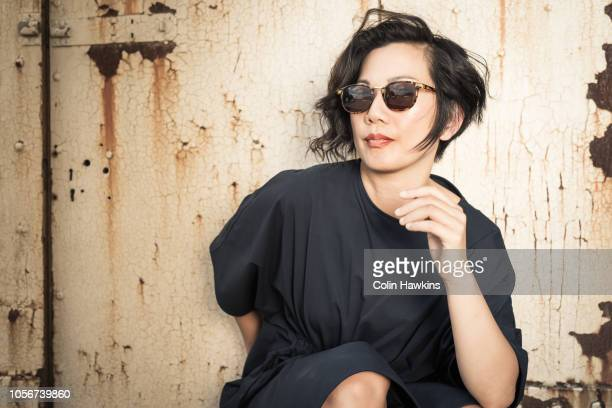Chinese woman outside industrial building wearing sunglasses