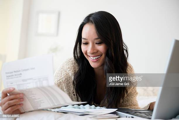 Chinese woman paying bills on laptop