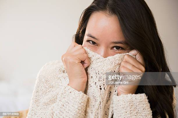 Chinese woman peeking over collar of sweater