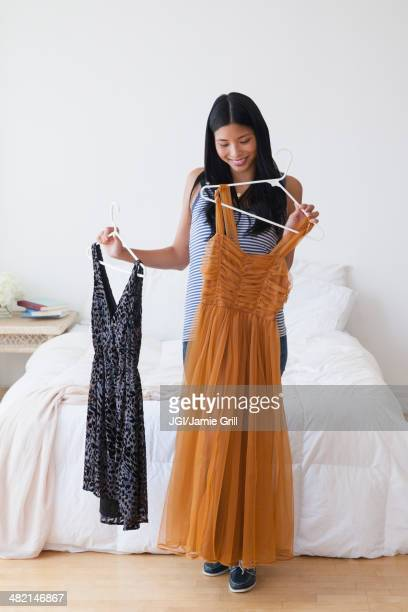 Chinese woman picking out dresses in bedroom