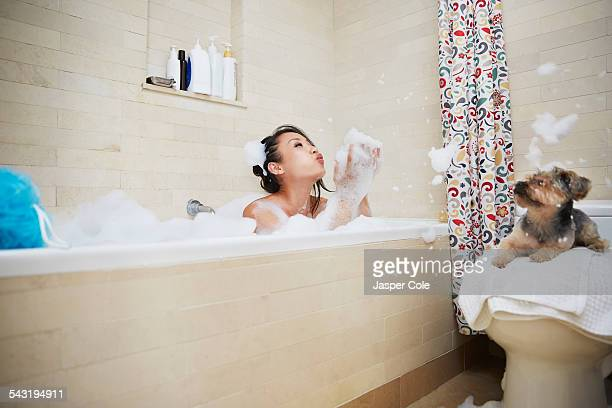 Chinese woman playing in bubble bath with dog