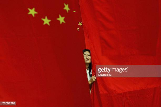 Chinese woman poses for a photo as she visits a national flag show decorated for the upcoming National Day celebrations at Chaoyang park on September...