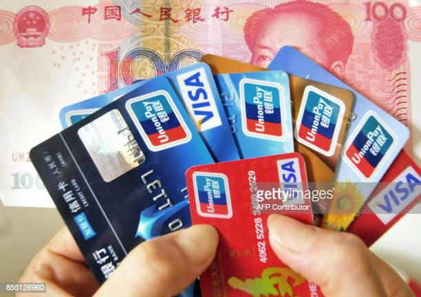 A Chinese woman poses with a handful of credit cards and a 100 yuan banknote Beijing on July 22 2010 Chinese banks will face rising bad loans in the...