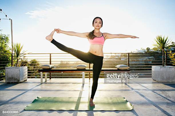 chinese woman practicing yoga on balcony - pretty asian feet stock photos and pictures
