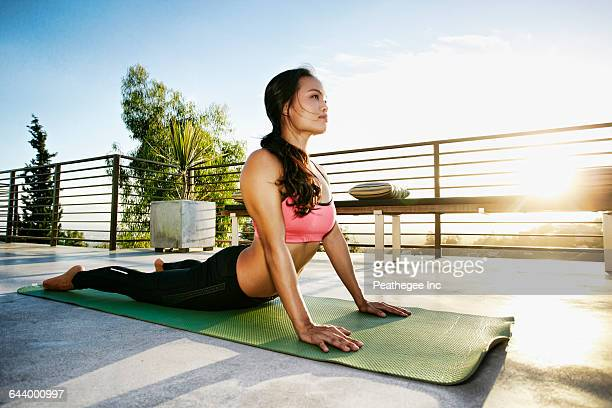 chinese woman practicing yoga on balcony - california strong stock photos and pictures