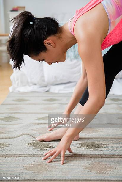 Chinese woman practicing yoga on carpet