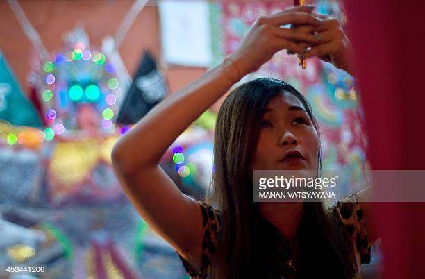 A Chinese woman prays in front of a statue made of paper of Chinese deity 'Da Shi Ye' or Guardian God of Ghosts during the Hungry Ghost festival in...