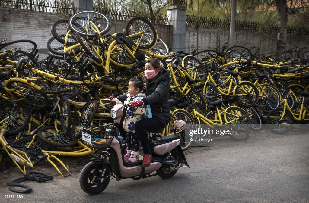 A Chinese woman rides with a child on a scooter past piles of damaged bicycles pulled off the streets by bike share company Ofo Inc. at a repair depot for the company on March 30, 2017 in Beijing, China. The popularity of bike shares has exploded in the past year with more than two dozen providers now battling for market share in major cities across China. The bikes are hailed as an efficient, cheap, and environmentally-friendly solution for commuters, where riders unlock the stationless bicycles using a mobile phone app, drop them anywhere for the next user, and spend as little as 1 yuan ($0.15) per hour. Given the bikes have several users a day - some of them inexperienced riders who swerve into traffic - they are often damaged, vandalized, or abandoned. Companies like Ofo routinely collect the battered two-wheelers and bring them to a makeshift depot that is part repair shop, part graveyard where they are either salvaged or scrapped. The bike shares are powering a cycling revival of sorts in a country once known as the 'Kingdom of Bicycles'. In the early years of Communist China, most Chinese aspired to own a bicycle as a marker of achievement. When the country's economic transformation made cars a more valued status symbol, the bicycle - a Chinese cultural icon - was mocked as a sign of backwardness. The bike share craze is also a boon for manufacturers who are now mass producing over a million bikes a month to meet demand, and the number of shared bike users will reach 50 million in China by the end of the year, according to Beijing-based BigData Research. Not everyone is cheering the revival though, as municipal officials are drafting new regulations to control the chaotic flood of bicycles on streets and sidewalks.