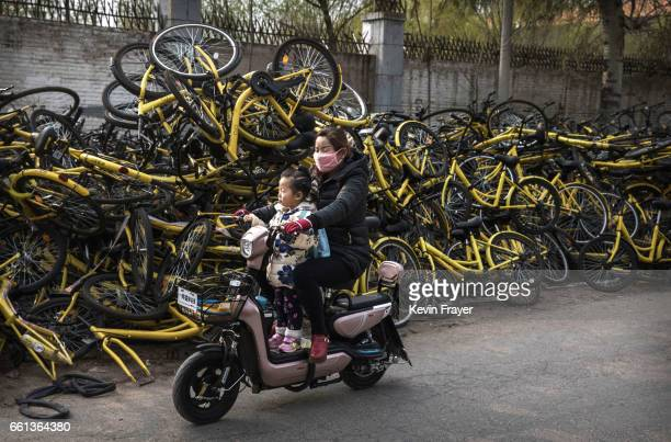 Chinese woman rides with a child on a scooter past piles of damaged bicycles pulled off the streets by bike share company Ofo Inc at a repair depot...