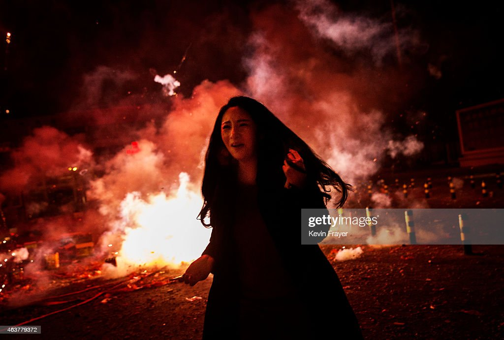 A Chinese woman runs away as she reacts as firecrackers she lit explode during celebrations of the Lunar New early on February 19, 2015 in Beijing, China.The Chinese Lunar New Year of Sheep also known as the Spring Festival, which is based on the Lunisolar Chinese calendar, is celebrated from the first day of the first month of the lunar year and ends with Lantern Festival on the Fifteenth day.