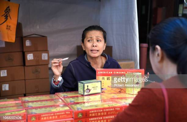 Chinese woman selling American ginseng tea at a street festival makes a sales pitch to a potential customer in Chinatown San Francisco California