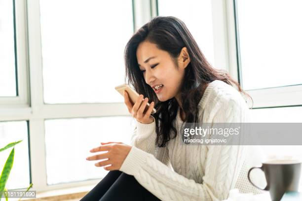 chinese woman sending voice message at home - speech recognition stock pictures, royalty-free photos & images