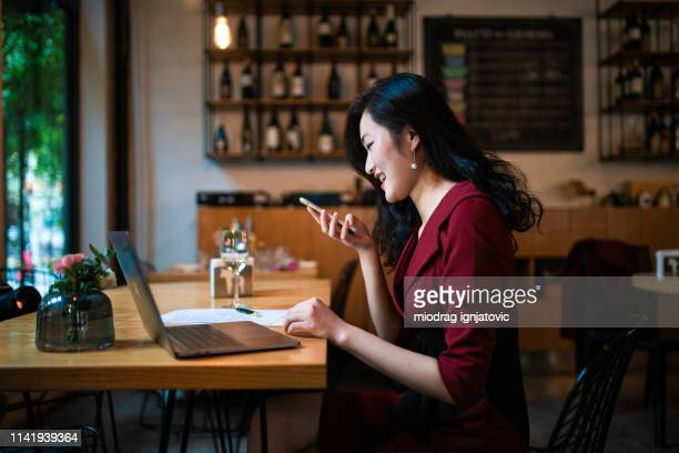 chinese woman sending voice message - speech recognition stock pictures, royalty-free photos & images