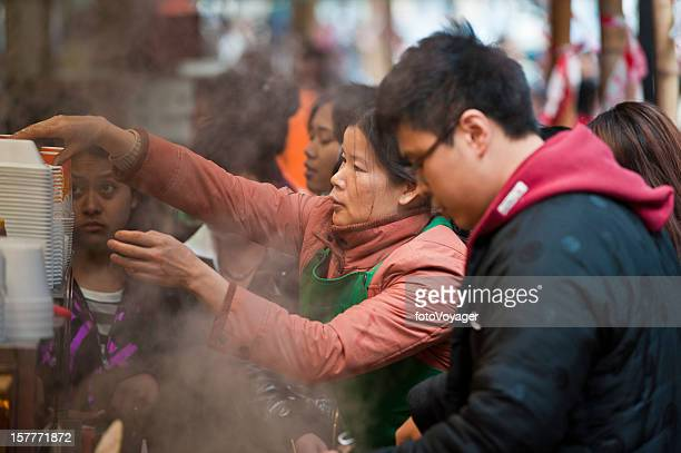 Chinese woman serving lunchtime crowd street food stall Hong Kong