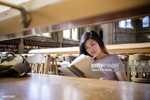 Chinese woman sitting in library reading book