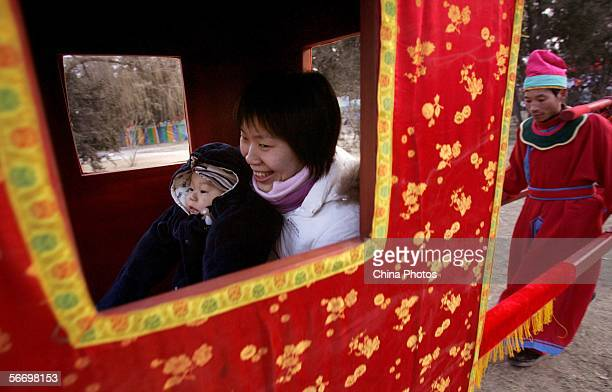 A Chinese woman smiles as she and her child sit in a Chinese traditional sedanchair during a temple fair at the Temple of Earth for Chinese New Year...