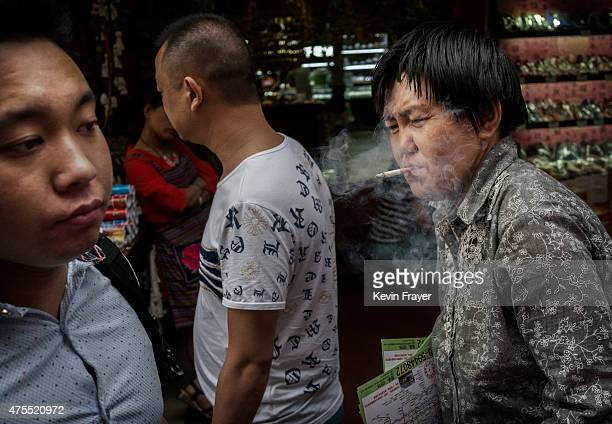Chinese woman smokes a cigarette in a prohibited area under tough new antismoking laws in a shopping market on June 1 2015 in Beijing China Beijing...