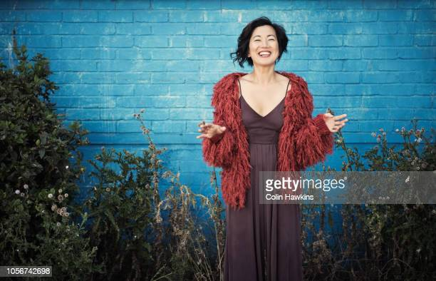Chinese woman standing outside industrial blue wall