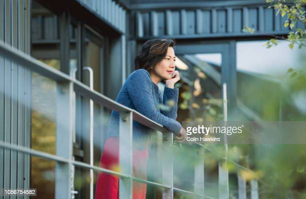 Chinese woman standing outside industrial building