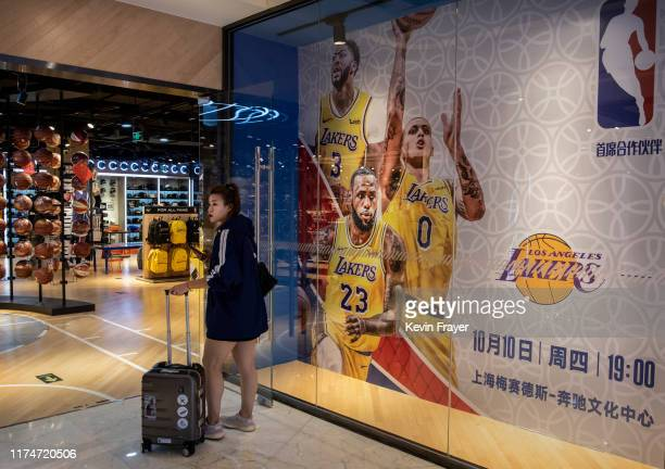 Chinese woman stands next to a billboard showing players from the Los Angeles Lakers and advertising their upcoming exhibition game against the...