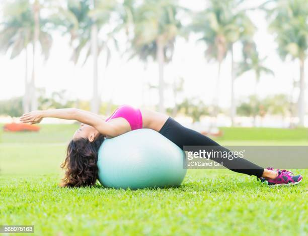 Chinese woman stretching on fitness ball in park