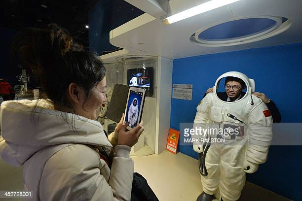 A Chinese woman takes a photo of her husband in an astronaut suit at the Science Museum in Beijing December 1 2013 China's state media and people...