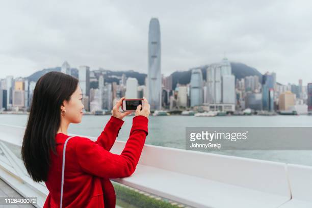 chinese woman taking photo of city on phone - photo messaging stock photos and pictures