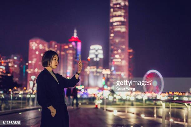 Chinese woman taking pictures with smartphone in city at night