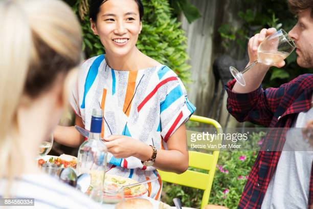 Chinese woman talks to friends at dinner party.