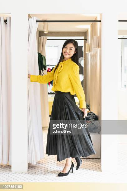 chinese woman trying on outfit in shop - skirt stock pictures, royalty-free photos & images