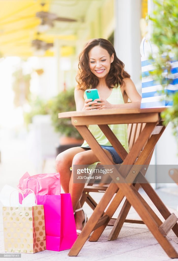 Chinese woman using cell phone at sidewalk cafe : Stockfoto