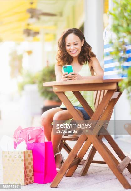 chinese woman using cell phone at sidewalk cafe - palm beach county stock photos and pictures