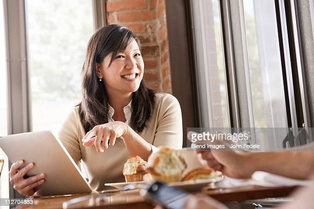 Chinese woman using digital tablet in cafe