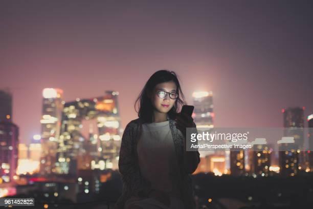 chinese woman using smartphone on skyscraper roof at night - front view bildbanksfoton och bilder
