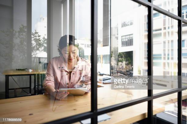 chinese woman using tablet in a glass office - singapore stock pictures, royalty-free photos & images