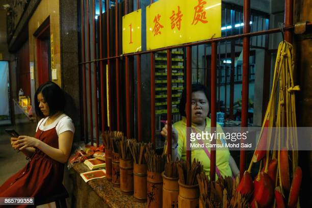 Chinese woman wait for devotees to buy prayer paper during The Nine Emperor Gods Festival inside the temple on October 24 2017 in Kuala Lumpur...