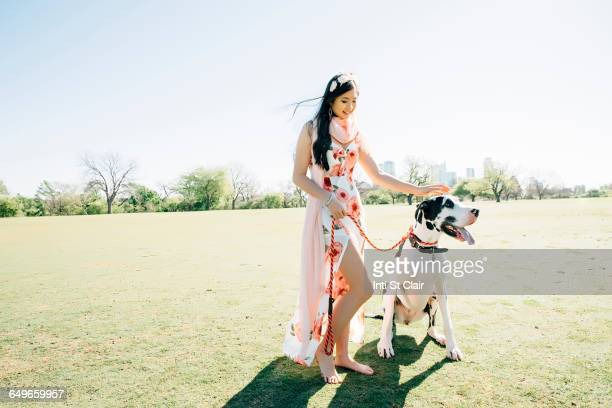 Chinese woman walking dog in field