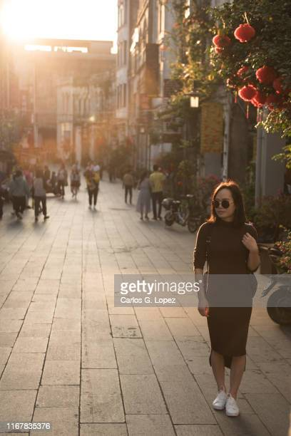 chinese woman walks along the old street in beihai, china - golden hour stock pictures, royalty-free photos & images