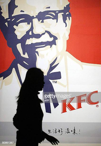 Chinese woman walks by a Kentucky Fried Chicken poster in downtown Beijing 24 June 2004 Exiled Tibetan spiritual leader the Dalai Lama has told the...