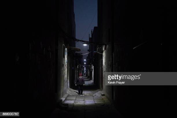 Chinese woman walks in an abandoned alleyway in an area that used to have migrant housing and factories on December 6 2017 in the Daxing District of...