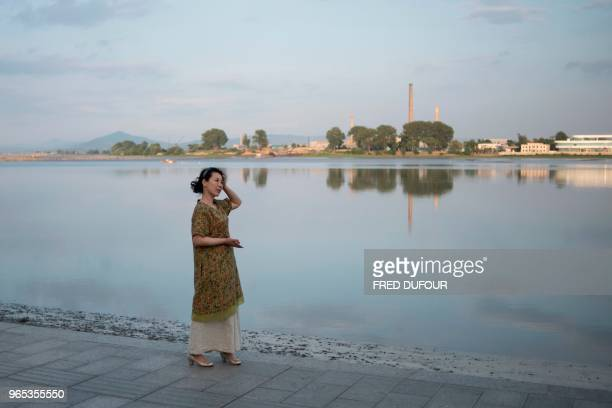 A Chinese woman walks on the banks of the Chinese border town of Dandong in China's northeast Liaoning province on May 30 2018 The city of Dandong...