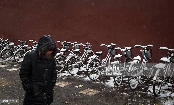Chinese woman walks passed bikes covered in snow during a snowfall on November 22 2014 in Beijing China China's capital and other parts of northern...