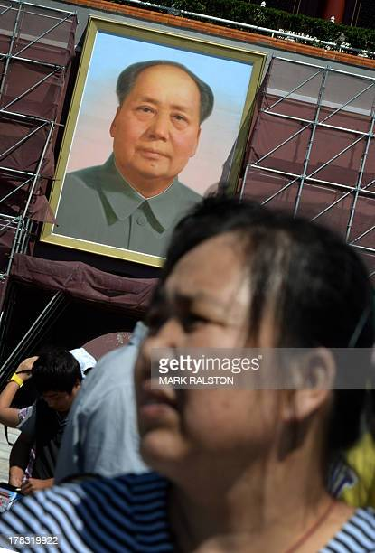 A Chinese woman walks past a portrait of the late leader Mao Zedong on Tiananmen Gate which is undergoing renovation in Beijing on August 29 2013 The...