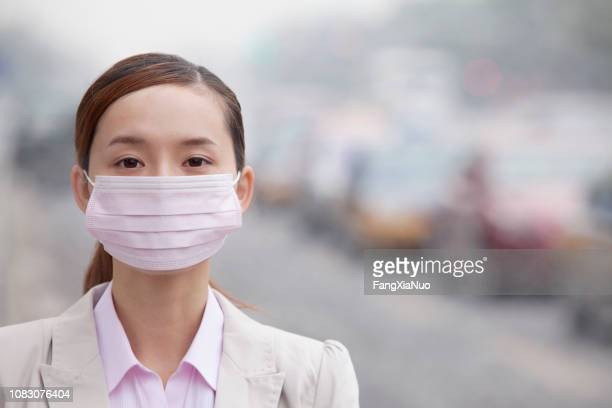 chinese woman wearing face mask because of air pollution in the city - epidemic stock pictures, royalty-free photos & images