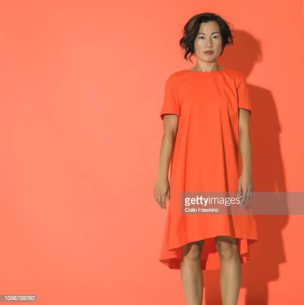 Chinese woman wearing orange dress on orange background