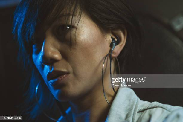 Chinese woman wearing small headphones at night in club