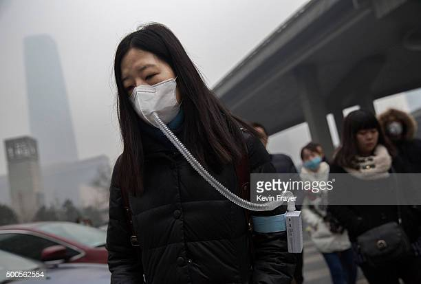 A Chinese woman wears a mask and filter as she walks to work during heavy pollution on December 9 2015 in Beijing China The Beijing government issued...